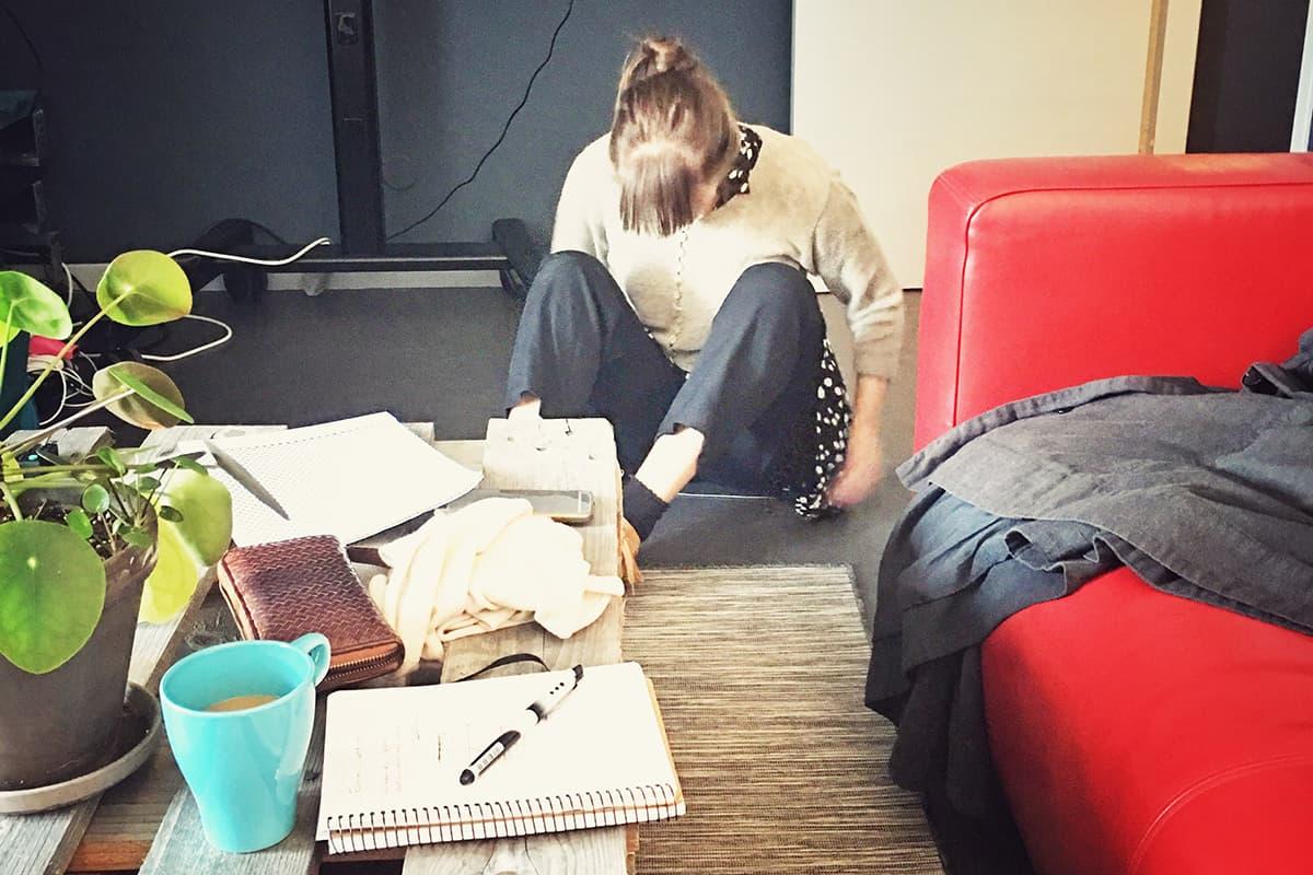 Amalia sitter på golvet och testar material till Heather